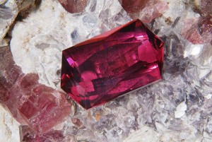 Faceted Rubellite (red tourmaline) from Morro Redondo, Minas Gerais, Brazil; sitting on a piece of pegmatite containing rough rubellite crystals, quartz and lepidolite mica.