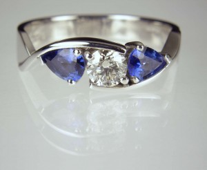 Round brilliant cut diamond 0.42ct set with a matched pair of pear cut sapphires totalling 0.8ct mounted in platinum