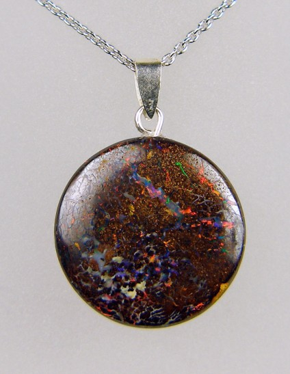 22.62ct round boulder opal pendant in silver - 22mm round boulder opal pendant with vivid colour flashes in orange and red, with silver bail on adjustable silver chain