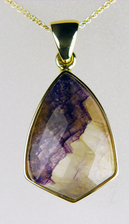 "Blue John pendant in 18ct yellow gold - Faceted Blue John pendant in 18ct yellow gold on delicate 20"" fine trace chain. Blue John is a variety of fluorspar found only in Castleton in Derbyshire."
