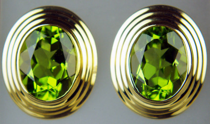 Peridot oval earstuds in 9ct yellow gold - 3.75ct pair of fine quality oval peridots set in an elegant gold ribbed rubover setting. Earstuds are 14x12mm. Mounts are 9ct yellow gold.