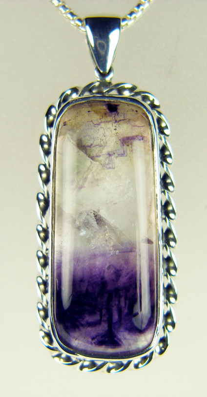 "Blue John pendant in silver - Large pendant (45 x 22mm) in silver with ornamental surround, cabochon of Derbyshire fluorspar known as 'Blue John' backed with mother of pearl and suspended from a 18"" silver chain."