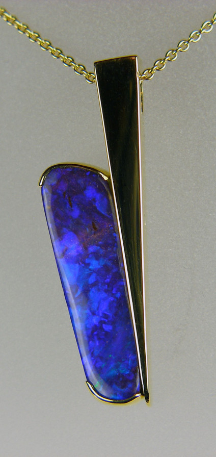 "Boulder opal pendant in 18ct yellow gold - 4.82ct brilliant purple-blue boulder opal set in a handmade angular 18ct yellow gold pendant mount and suspended from a 21"" adjustable fine trace chain in 18ct yellow gold"