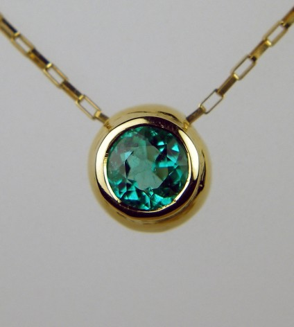 Round emerald pendant - simple rubover set Colombian emerald 0.57ct in 18ct yellow gold on delicate 18ct yellow gold chain