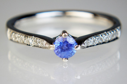 Sapphire ring with diamond set shoulders in 18ct white gold - 0.31ct round sparkly natural blue sapphire set in an 18ct white gold ring with 16pt of graduated size brilliant cut diamonds pave set down the ring shoulders. Ring size O. Rings with diamond set shoulders can be difficult to resize.