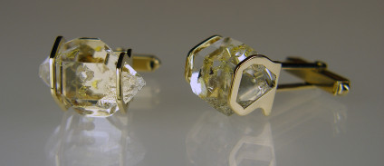 Rare oil included quartz crystals in 9ct yellow gold - Cufflinks in 9ct yellow gold (smaller pair). Rare oil included quartz crystals from Balochistan are set in individually handmade gold mounts.  The crystals are approximately 2-3cm in all dimensions and contain golden droplets of light oil, along with darker bitumen and an aqueous solution.  The inclusions fluoresce a strong bluish green under UV light.  Each pair of cufflinks comes with a UV pen torch and an explanation of the crystal.  These crystals are extremely rare and it is difficult to find such perfect examples as sold by Just Gems.  The setting is precisely made to fit each unique crystal and has to be created without the application of heat, which could cause the crystal to fracture.  Each piece is handmade in Scotland and hallmarked in Edinburgh. Pendants and earrings also available.  A selection of crystals are available for bespoke designs.