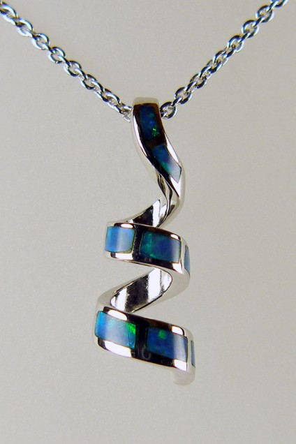 """Silver spiral pendant set with inlaid black opal - Pretty silver pendant inlaid with Australian solid black opal. The pendant has been rhodium plated to resist tarnishing and is suspended from a rhodium plated silver chain of adjustable length 15-22""""."""