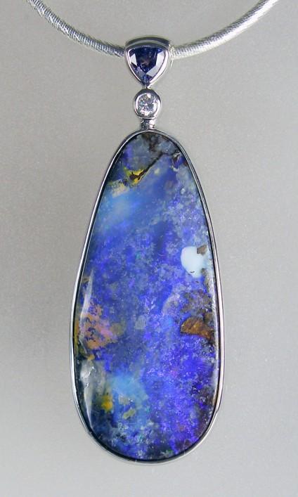 Boulder opal, sapphire & diamond pendant in silver - 54.94ct pear shaped Australian boulder opal set with 0.70ct triilion cut purple sapphire & 0.12ct round brilliant cut diamond in a rubover silver pendant