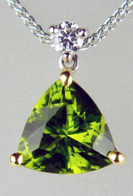 Peridot & diamond pendant in 18ct white & yellow gold - 2.62ct trillion cut green peridot set with a 0.10ct round brilliant cut white diamond G/VS in 18ct yellow and white gold suspended from a delicate spiga chain in 18ct white gold