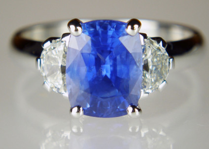 Sapphire & half moon diamond ring in 18ct white gold - Lady's dress ring in 18ct white gold set with 3.32ct cushion cut blue sapphire from Sri Lanka and flanked by a matched 0.59ct pair of G/VS half moon diamonds.