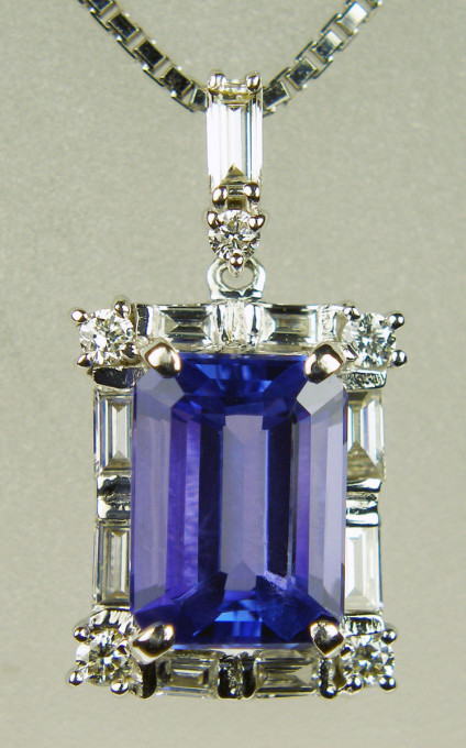 Tanzanite & diamond pendant in 18ct white gold - 2.55ct emerald cut tanzanite flanked by 0.32ct of baguette and round brilliant cut diamonds in H colour SI clarity and mounted in 18ct white gold on a length adjustable 18ct white gold chain. Pendant is 20mm long and 10mm wide
