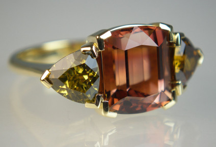 Tourmaline & garnet ring - Fancy cut 4.61ct brown tourmaline flanked by a pair of trillion cut garnets weighing 2.15ct (garnets are deliberately mismatched - one is chartreuse green and the other a single malt whisky coloured golden brown), set as a ring in 18ct yellow gold. Contemporary, striking and unusual dress ring in autumnal colours.