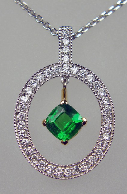 "Tsavorite & diamond pendant - 0.46ct cushion cut tsavorite garnet set in 18ct yellow gold and surround with a halo of 0.29ct round brilliant cut diamonds set in 18ct white gold. Suspended from a 16"" fine trace chain."