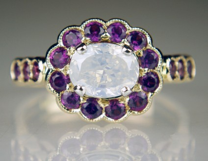 Milk white opalescent diamond & purple sapphire ring - 1ct oval milky white opalescent diamond surrounded by a halo of magenta purple sapphire rounds weighing 0.88ct and all mounted in an exquisite handmade 18ct rose gold ring